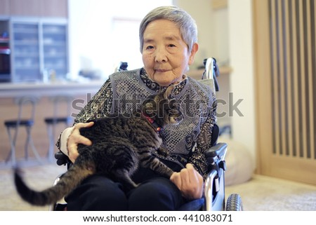 Senior woman in a wheelchair and cat in the room - stock photo