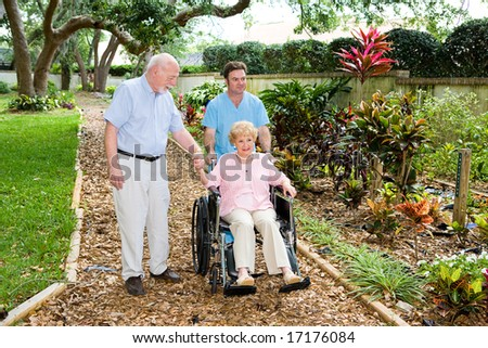 Senior woman in a wheelchair being walked through the nursing home garden by an orderly and her husband. - stock photo