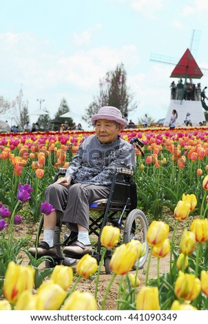 Senior woman in a wheelchair in the flower park