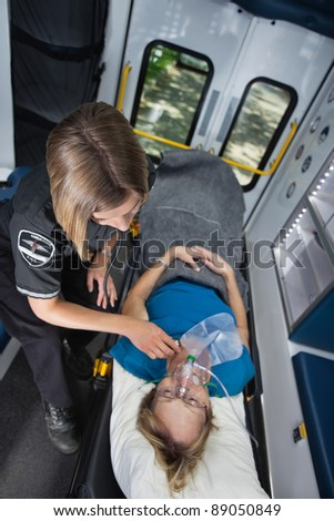 Senior woman in ambulance receiving emergency medical care - stock photo