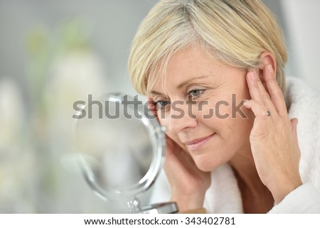 Senior woman in bathroom applying anti-aging lotion - stock photo