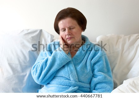 Senior woman in bed with toothache - stock photo