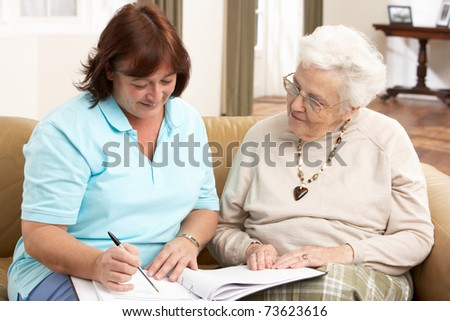 Senior Woman In Discussion With Health Visitor At Home - stock photo