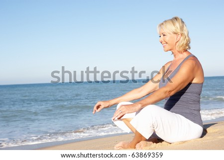 Senior Woman In Fitness Clothing Meditating On Beach - stock photo
