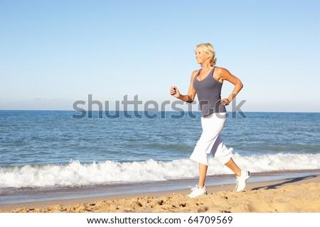 Senior Woman In Fitness Clothing Running Along Beach - stock photo