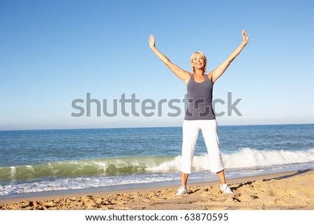 Senior Woman In Fitness Clothing Stretching On Beach - stock photo