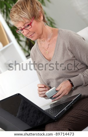 Senior woman in front of a laptop at home - stock photo
