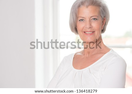 Senior woman in front of a white window