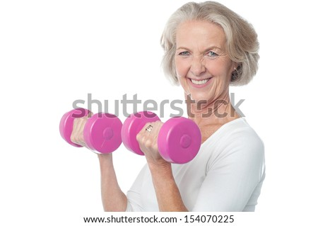 Senior woman in gym working out with dumbbells - stock photo