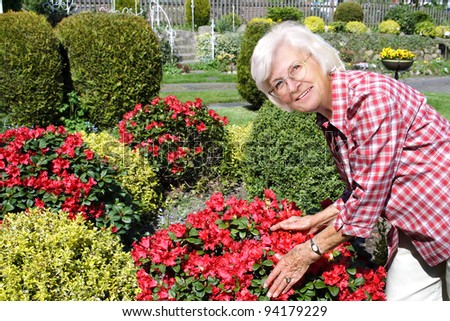 Senior woman in her garden with bushes and flowers - stock photo
