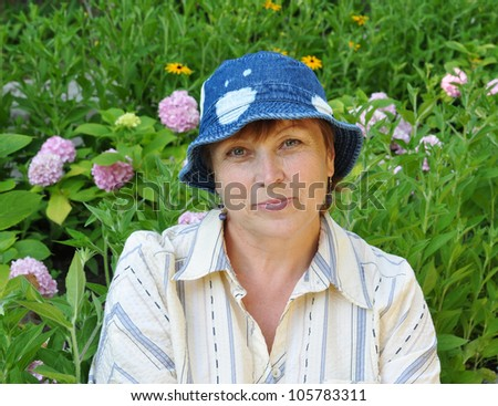 Senior woman in jeans panama sitting in her garden near beds with hydrangeas
