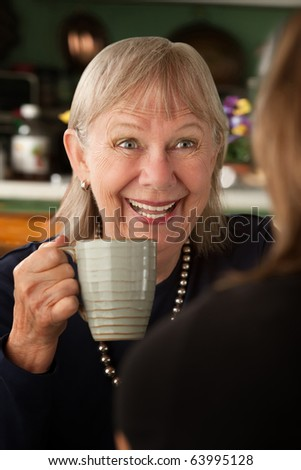 Senior woman in kitchen talking with daughter or friend
