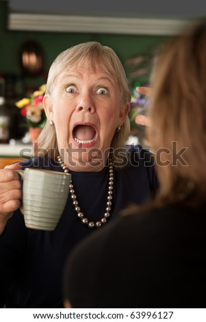 Senior woman in kitchen talking with daughter or friend - stock photo