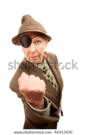 Senior woman in male clothing and eyepatch making a fist