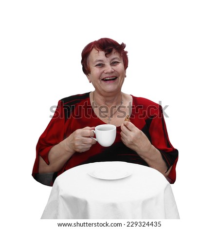 Senior woman in red dress sits behind table with coffee cup and cookie in hands and laughs. Portrait isolated on white background - stock photo