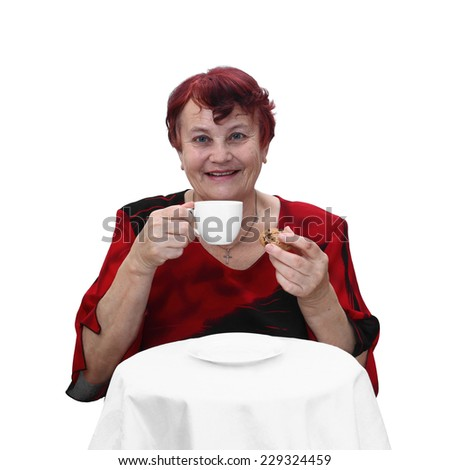 Senior woman in red dress sits behind table with coffee cup and cookie in hands and smiles. Portrait isolated on white background - stock photo