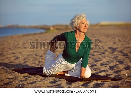 Senior woman in stretching position by the sea at morning. Elderly woman doing yoga on the beach. - stock photo