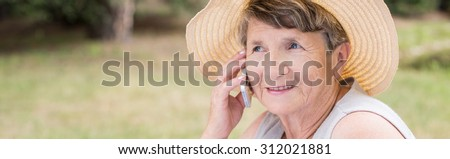 Senior woman in summer straw talking on the phone