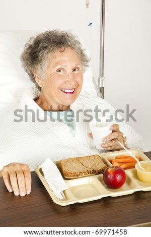 Senior woman in the hospital, eating her lunch from a tray.