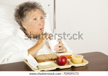 Senior woman in the hospital, eating lunch and drinking from a straw. - stock photo