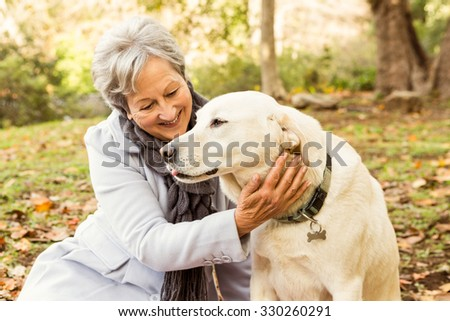 Senior woman in the park on an autumns day - stock photo