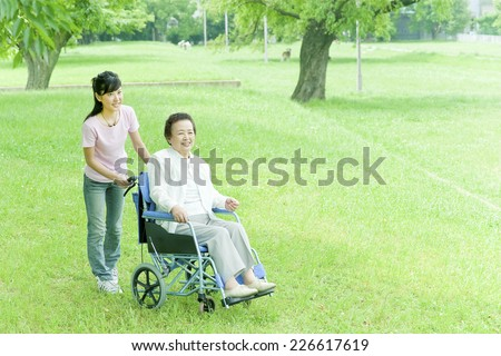 Senior woman in wheelchair being pushed by young woman - stock photo