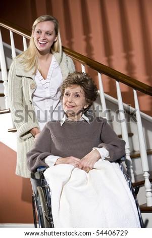 Senior woman in wheelchair with nurse helping - stock photo
