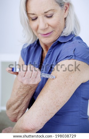 Senior woman injecting herself with insulin. - stock photo