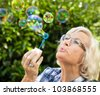 Senior woman is blowing bubbles in the garden,close-up - stock photo