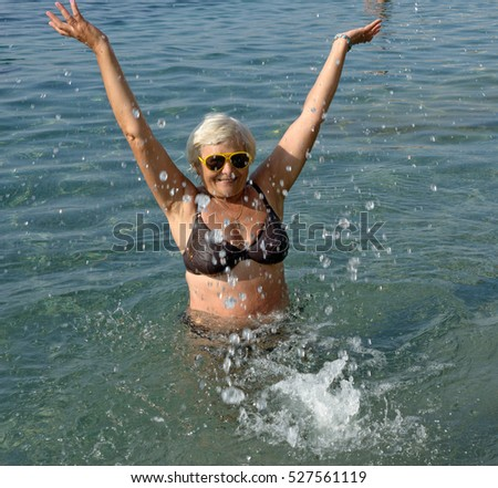 Senior woman is doing spa splashing exercises in light clear water of sea in sunlight.