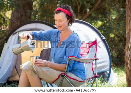 senior woman is sitting beside her tent in a forest