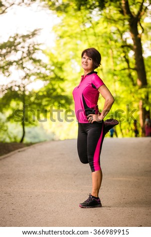 Senior woman is stretching before jogging outdoor in park