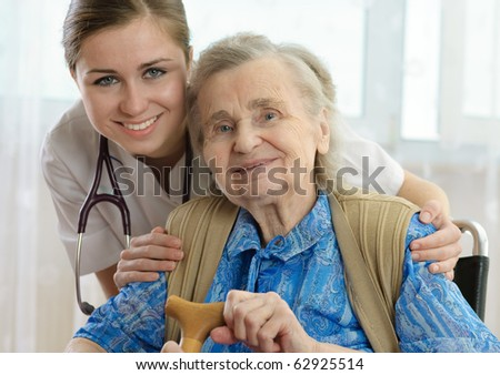 Senior woman is visited by her doctor or caregiver - stock photo