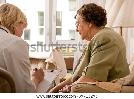 Senior woman is visited  by her doctor or caregiver at home - stock photo