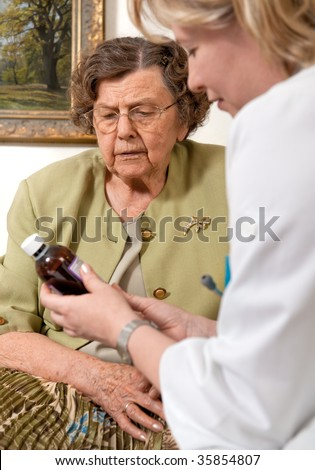 Senior woman is visited home by her doctor or caregiver at home. In the background is a picture from my portfolio - stock photo