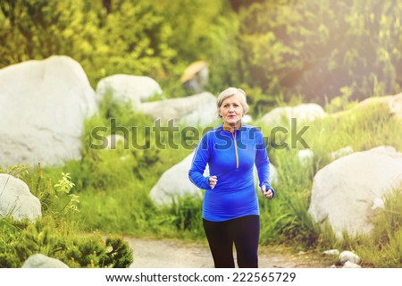 Senior woman jogging in beautiful nature, rocks in background - stock photo