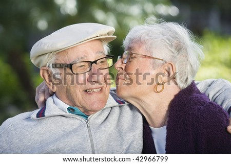 Senior woman kissing senior man on the cheek. Horizontally framed shot. - stock photo
