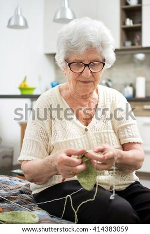 Senior woman knitting at home. - stock photo