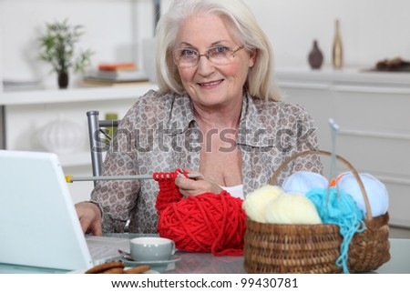 Senior woman knitting in front of her laptop computer - stock photo