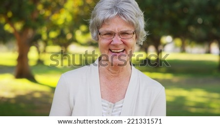 Senior woman laughing at the park - stock photo