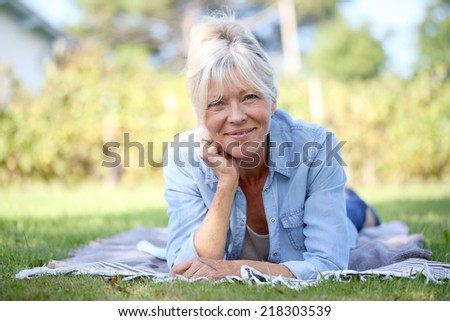 Senior woman laying in garden and relaxing - stock photo