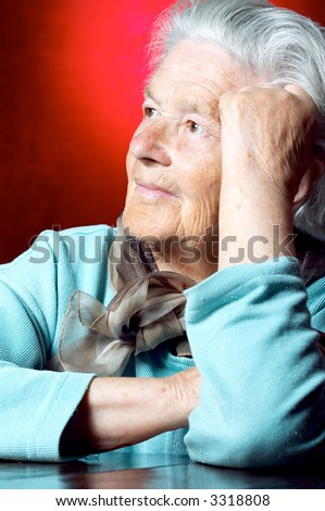 Senior woman leaning on hand and contemplating - stock photo
