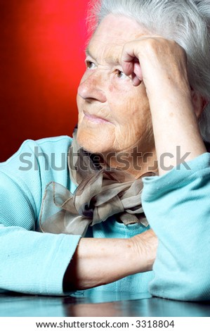 Senior woman leaning on hand and looking away - stock photo
