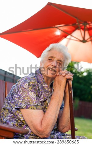 Senior woman leaning on her stick - stock photo