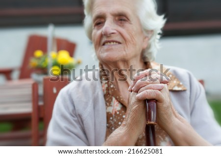 Senior woman leaning on her stick / cane - stock photo