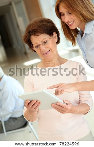 Senior woman learning how to use electronic tablet - stock photo