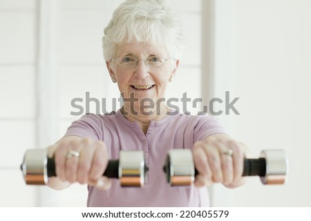 Senior woman lifting free weights - stock photo
