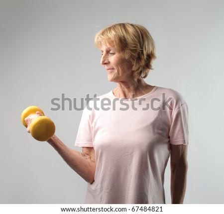 Senior woman lifting weights - stock photo