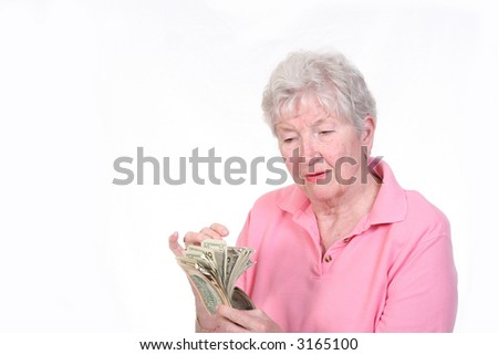 Senior woman looking concerned while counting a hand full of money - stock photo