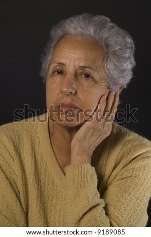 Senior woman looking depressed on black background - stock photo